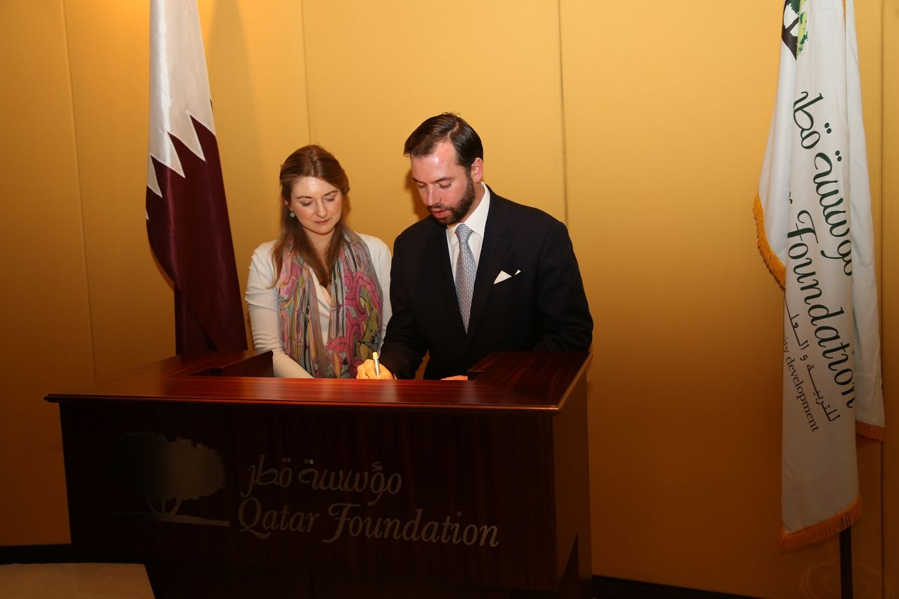 His Royal Highness Crown Prince Guillaume of Luxembourg, standing alongside Her Royal Highness Crown Princess Stéphanie of Luxembourg, signing the Qatar Foundation Visitor's Book.