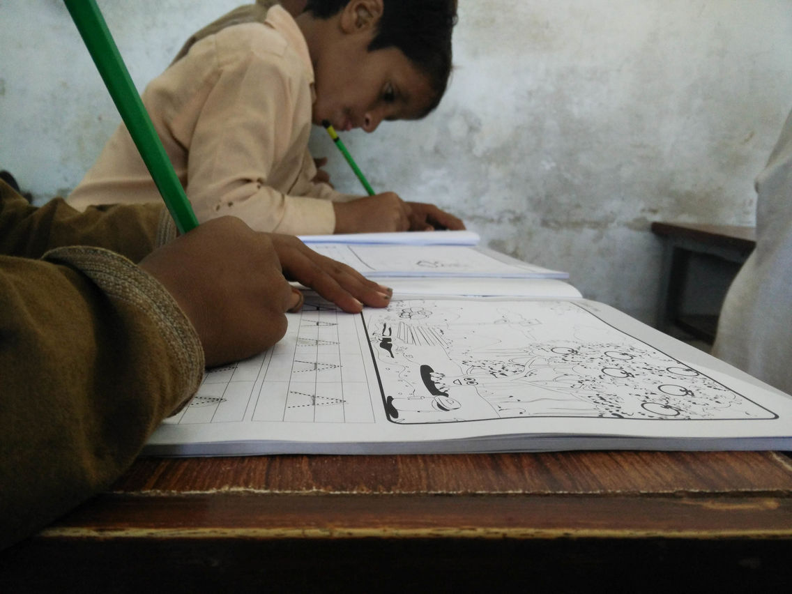 Students in Pakistan using the books that accompany Orenda's educational Taleemabad cartoon program.jpg